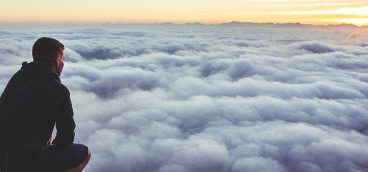 Ein Mann hockt auf einem Berg und schaut auf die Wolken unter sich.